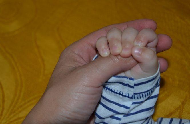 mana de copil si mana de adult - imbratisare - incredere